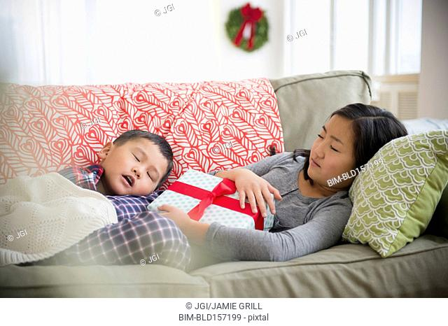 Asian brother and sister napping on sofa with Christmas gift