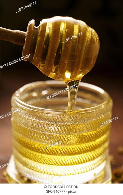 Honey running from honey dipper into honey jar