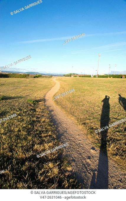 Two shadows of people walking along the path in the Sculpture park of the Tower of Hercules, A Coruña, Galicia, Spain, Europe