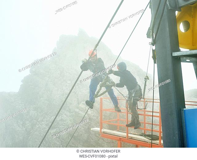 Germany, Bavaria, Garmisch-Partenkirchen, Zugspitze, installers working on steel rope of a goods cable lift