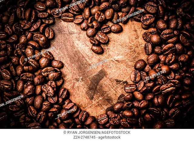 Closeup of coffee beans in the shape of heart on wooden table