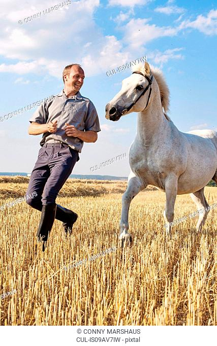 Male trainer running in front of white horse in field