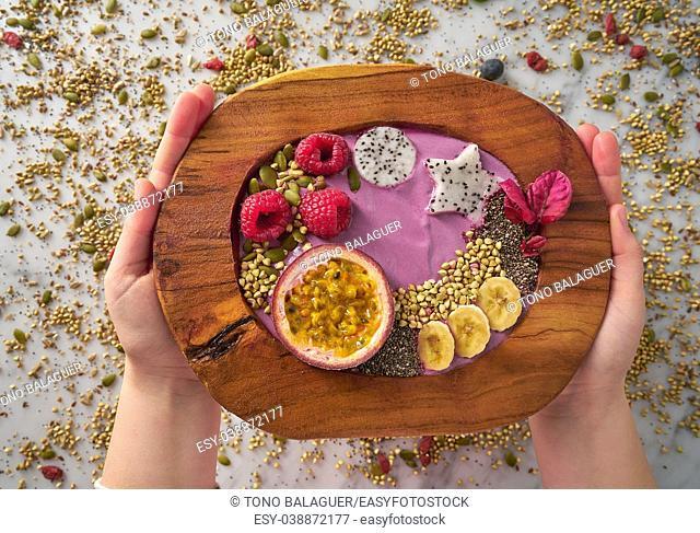 Acai bowl smoothie with passion fruit maracuya seeds banana and raspberries