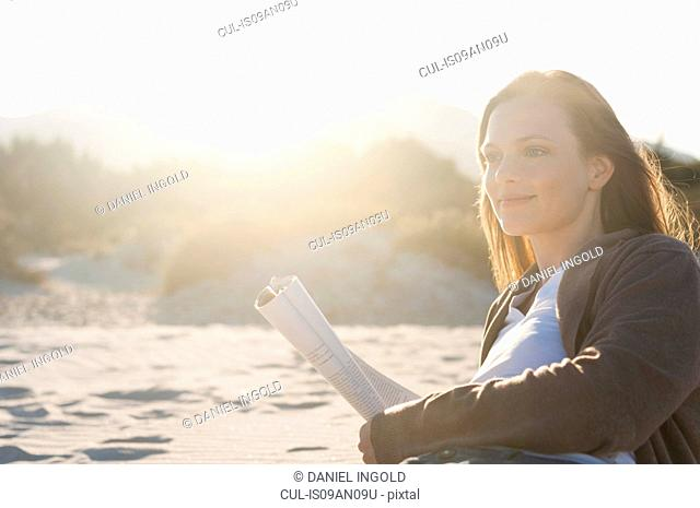 Mid adult woman reading newspaper on beach, Sardinia, Italy