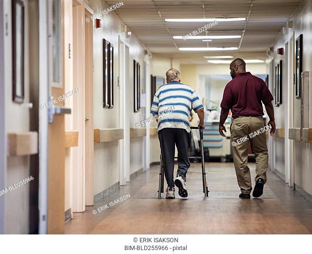 Nurse walking with patient using walker