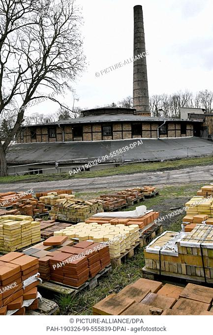 26 March 2019, Brandenburg, Glindow: Bricks are stacked in front of the historic kiln on the premises of the brick factory