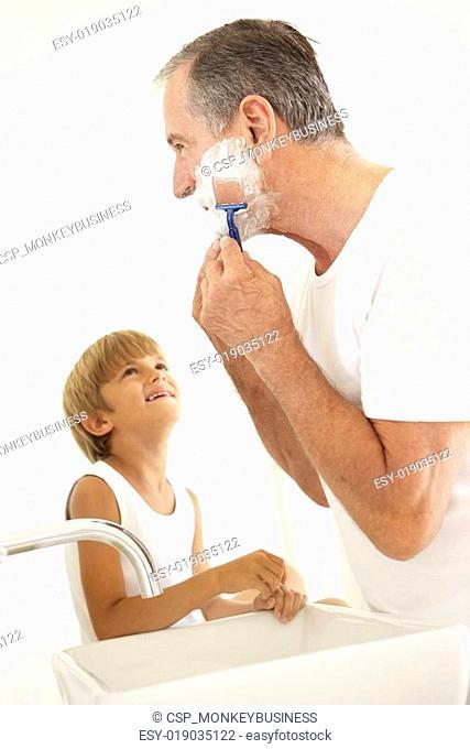 Grandson Watching Grandfather Shaving In Bathroom Mirror