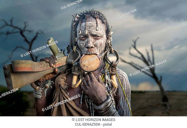 Woman of the Mursi tribe with Kalashnikov gun, Omo Valley, Ethiopia