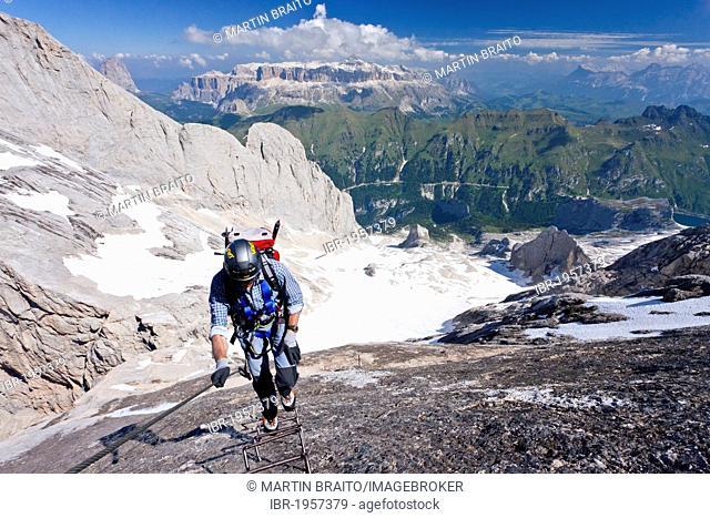 Mountain climber ascending Marmolada Mountain on the Westgrat climbing route, view towards Sella Mountain, the Heiligkreuzkofelgruppe range