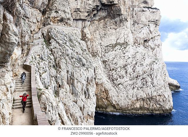 Two women walking on staircase amidst Capo Caccia cliffs. Alghero, Sardinia. Italy