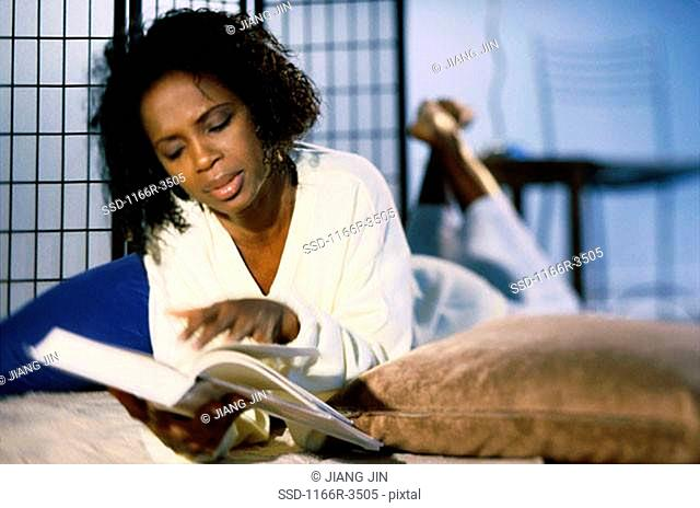 Young woman lying on a bed reading a book