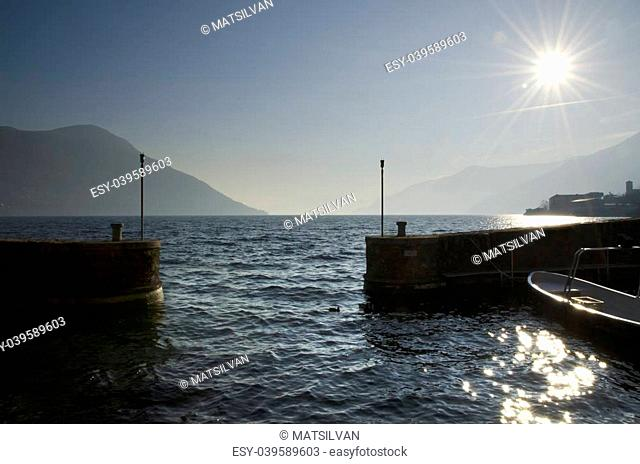 Small port in backlight with sunbeam and with boats and mountain