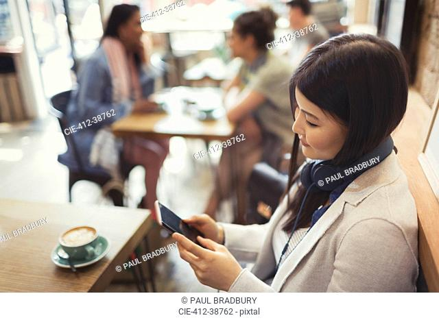 Young woman with headphones texting with cell phone and drinking coffee at cafe table