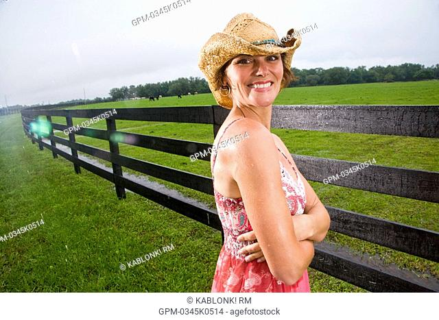 Portrait of young cowgirl in cowboy hat standing in front on fence on farm