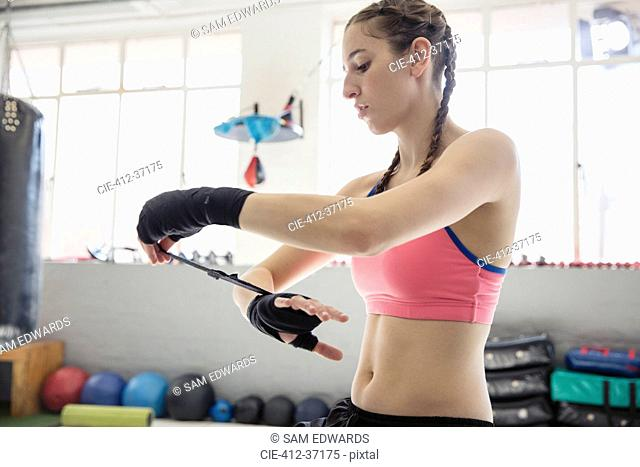 Young female boxer wrapping wrists in gym