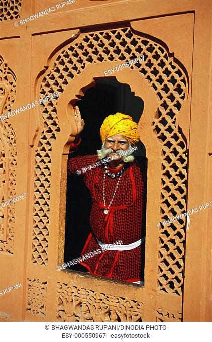 Folk musician standing in window , Rajasthan , India MR657