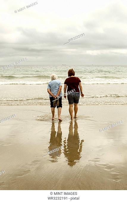Rear view of a grey haired elderly woman and a younger woman paddling with shoes off in shallow waves on a sandy beach