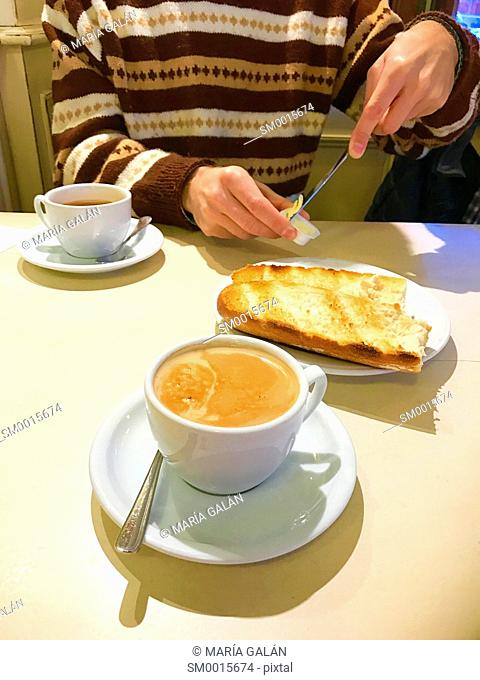 Man spreading butter on toast at breakfast