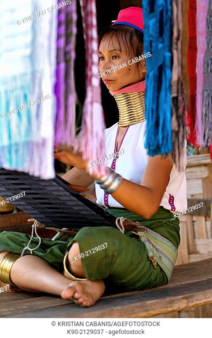 Longneck Karen woman sitting on the floor and weaving a pink scarf, Mae Hong Son, Thailand, Southeast Asia