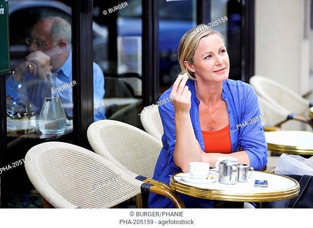 Woman drinking coffee at coffeeshop terrace