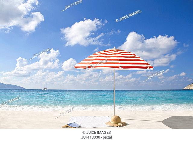 Sun hat and book on sunny beach under striped beach umbrella