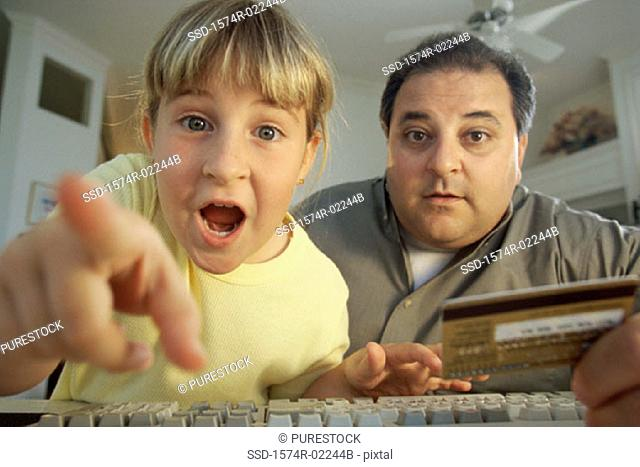 Portrait of a girl and her father in front of a computer