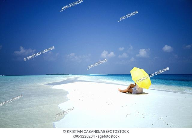 Young caucasian woman laying on the sandy beach with yellow umbrealla, Dharavandhoo, Baa Atoll, Maldives, Indian Ocean, South Asia