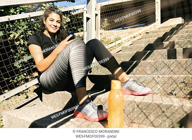 Sporty young woman having a break listening to music