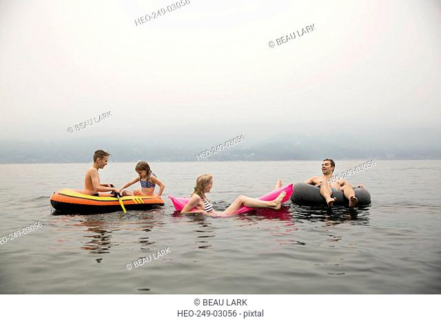 Family relaxing in pool rafts in lake