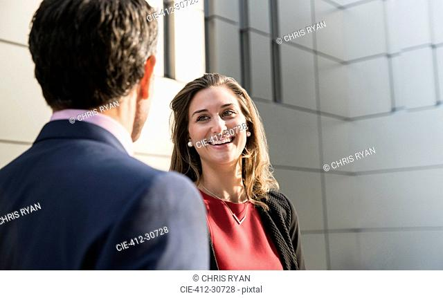 Corporate businesswoman smiling and talking to businessman