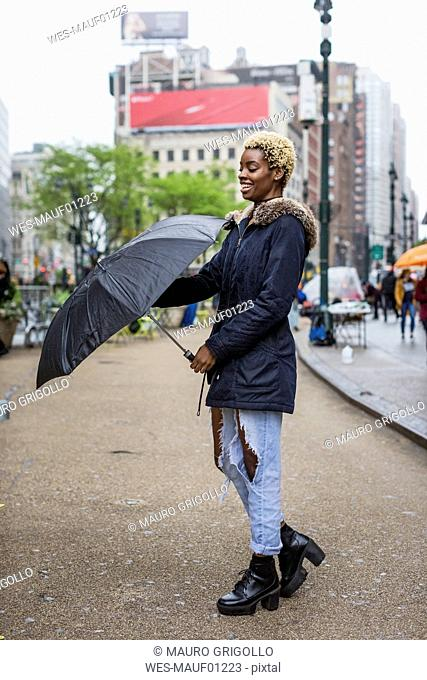 USA, New York City, portrait of laughing young woman with umbrella