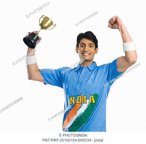 Cricket player celebrating his success with a trophy