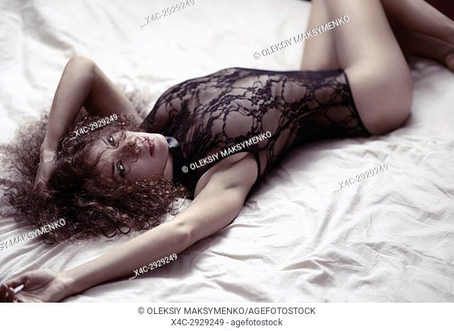 Sensual boudoir portrait of a sexy young beautiful woman lying on a bed in lacy underwear looking at camera