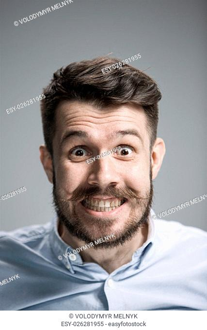 Man wearing a blue shirt is looking scared. Over gray background