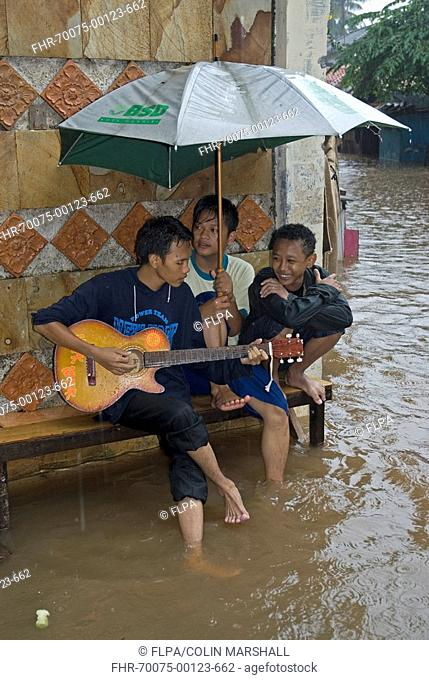 Flood victims, boy playing guitar underneath umbrella, Pejaten, Jakarta, Java, Indonesia