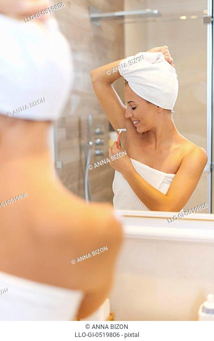 Woman shaving armpit after the shower. Debica, Poland