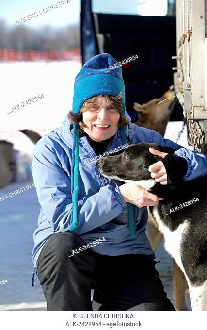 Alaska Iditarod Musher Cindy Gallea #42 poses with one of her dogs from her team just before the 2014 Iditarod restart, Willow, Alaska