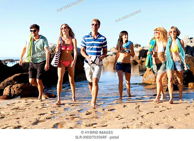 Smiling friends walking on beach