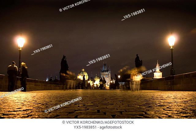 Pedestrian walking on Charles Bridge in Prague at night