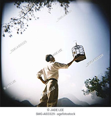 Man holding up birdcage