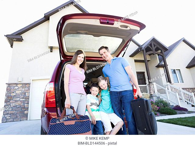 Caucasian family holding suitcases by car