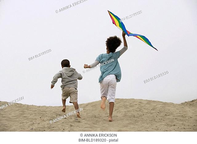 Mixed race children running on beach with kite