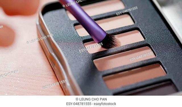 Palette with eye shadows and a makeup brush