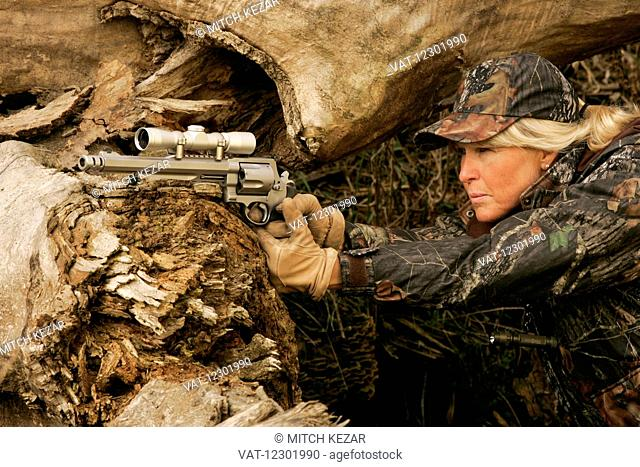 Female big game hunter with a scoped handgun
