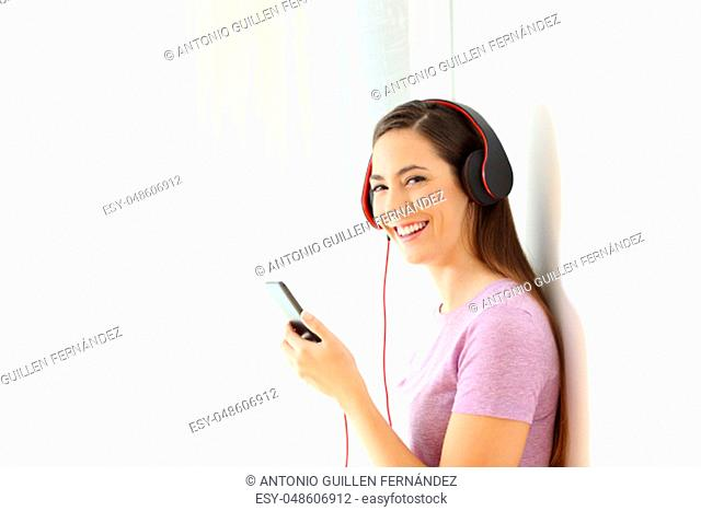 Happy female listening to music and looking at camera with an isolated background on white at side