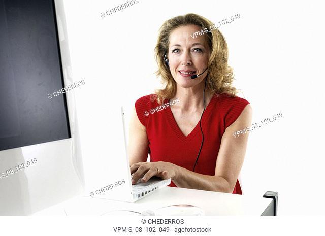 Portrait of a female customer service representative using a laptop