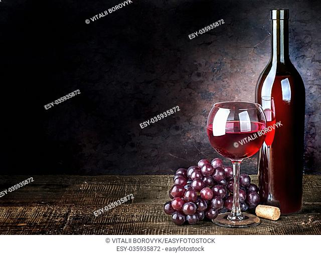 Glass of red wine with grapes and bottle on a wooden table