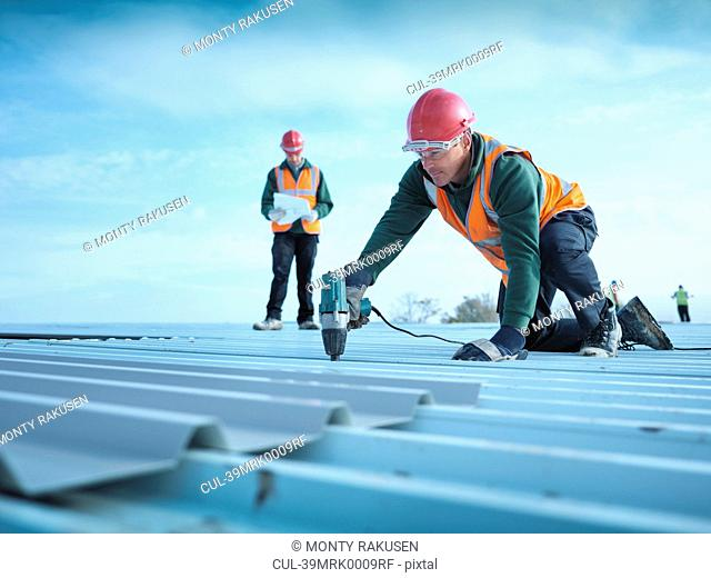 Worker drilling holes in roof