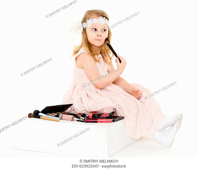 Pretty little girl playing with cosmetics on a white background. 3 year old