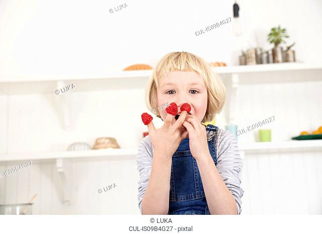 Portrait of cute girl with raspberries on her fingers in kitchen